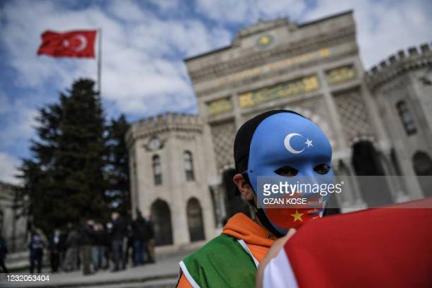 Demonstrator wears a mask painted with the colours of the flag of East Turkestan during a protest by supporters of the Uighur minority on April 1,...
