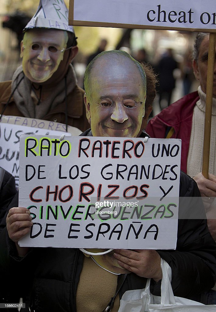 A demonstrator wears a mask while holding a sign during a protest against Rodrigo Rato, former managing director of the International Monetary Fund and ex-chairman of Bankia Group, as he testifies at Spain's national court in Madrid, Spain, on Thursday, Dec. 20, 2012. Rato who led the seven-way savings bank merger in 2010 that formed Bankia, has appeared before lawmakers probing how the lender that was nationalized after seeking 23.5 billion euros ($28.5 billion) of state aid helped trigger a new stage of Europe's debt crisis. Photographer: Angel Navarrete/Bloomberg via Getty Images