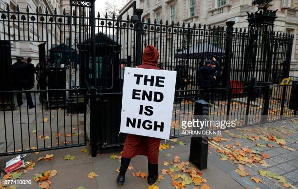A demonstrator wears a placard as he protests outside the entrance to Downing Street in London on November 22 before Britain's Chancellor of the...