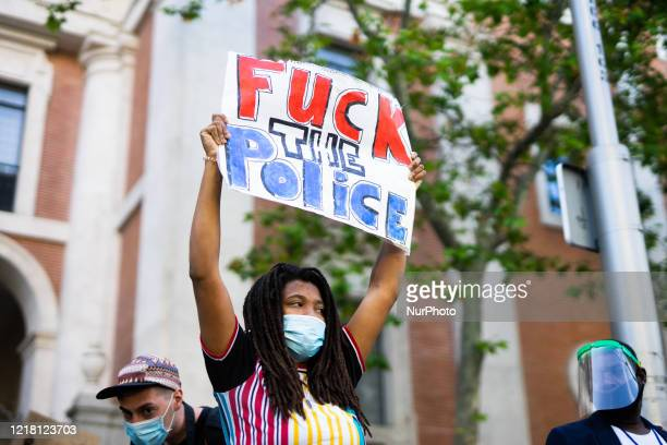 Demonstrator wears a protective mask as she holds a placard reading 'Fuck the police.' during a Black Lives Matter protest following the death of...