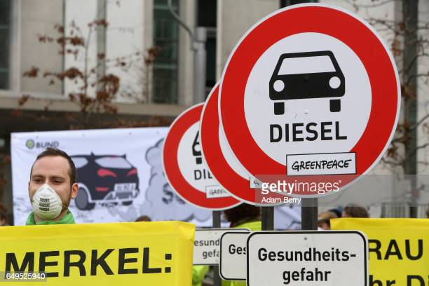 A demonstrator wears a respiratory mask reading 'Diesel Causes Cancer' in German outside of a German federal parliament or Bundestag hearing on the...