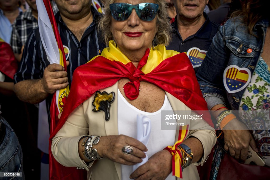 A demonstrator wears a Spanish national flag and wrist tie in support of Spanish unity during a march on Spain's National Day in Barcelona, Spain, on Thursday, Oct. 12, 2017. Prime Minister Mariano Rajoy gave his Catalan antagonist Carles Puigdemont five days to clarify whether he has declared independence from Spain or not as the country prepared for its national holiday on Thursday. Photographer: Angel Garcia/Bloomberg via Getty Images