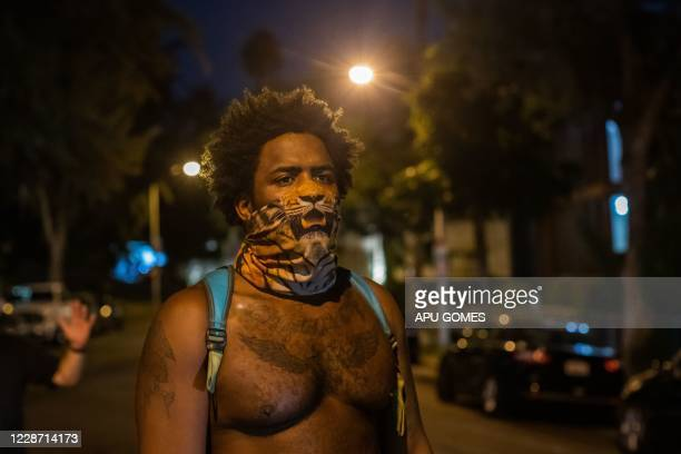 TOPSHOT A demonstrator wears a tiger scarf on his face during a protest over the lack of criminal charges in the police killing of Breonna Taylor in...