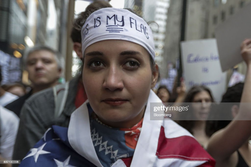 A demonstrator wears an American flag during the 'Defend DACA & TPS' rally outside of Trump Tower in New York, U.S., on Tuesday, Aug. 15, 2017. A day after belatedly faulting white supremacists for deadly clashes in Virginia, President Donald Trump returned to his controversial position that there was 'blame on both sides' for the weekend violence, saying that liberal counter-protesters also bore responsibility. Photographer: Jeenah Moon/Bloomberg via Getty Images