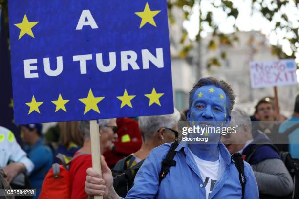 A demonstrator wears face paint in a European Union flag design as he holds a sign reading 'A EU TURN' ahead of the antiBrexit People's Vote march in...