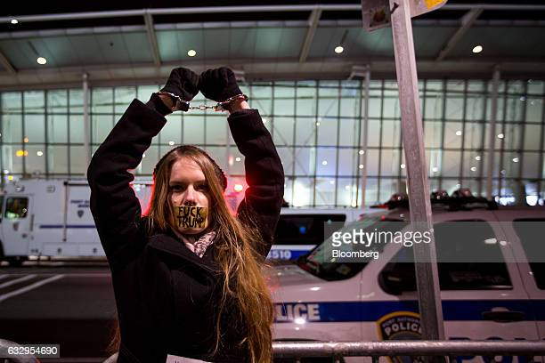 Image contains profanity A demonstrator wears handcuffs and tape over her mouth reading Fuck Trump during a protest outside John F Kennedy...