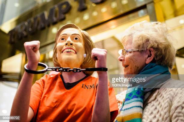A demonstrator wears prison scrubs and a Hillary Clinton mask outside Trump Tower in Midtown Manhattan in reference to repeated calls by Republican...