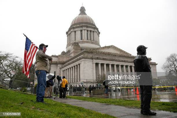 Demonstrator, who wished to remain anonymous, holds a US National flag as the Washington National Guard, State Patrol and a fence surround the state...