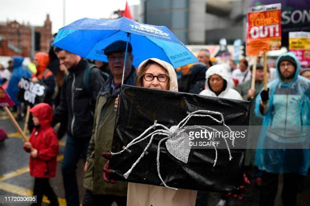 Demonstrator with a banner bearing a spider similar to the broach Lady Hale the president of the supreme court wore when she delivered the court's...