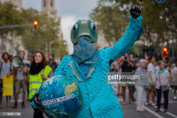 Demonstrator with a fish costume hold a world ball at the demonstration in Barcelona with the slogan 'The problem is not the weather the problem is...