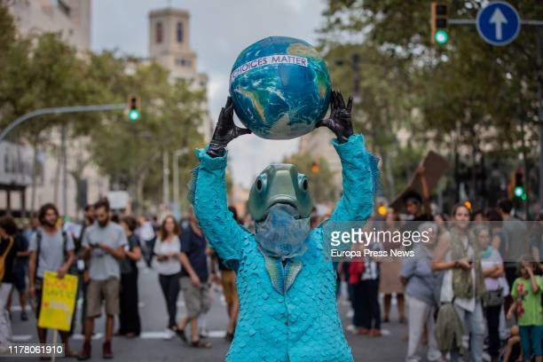 A demonstrator with a fish costume hold a world ball at the demonstration in Barcelona with the slogan 'The problem is not the weather the problem is...
