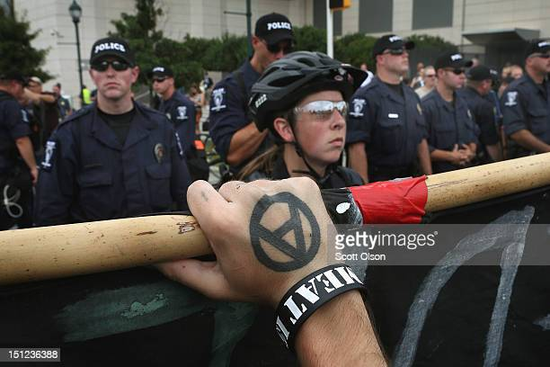 Demonstrator with an anarchy symbol on his hand holds a banner as police prevent a protest march from proceeding during the Democratic National...