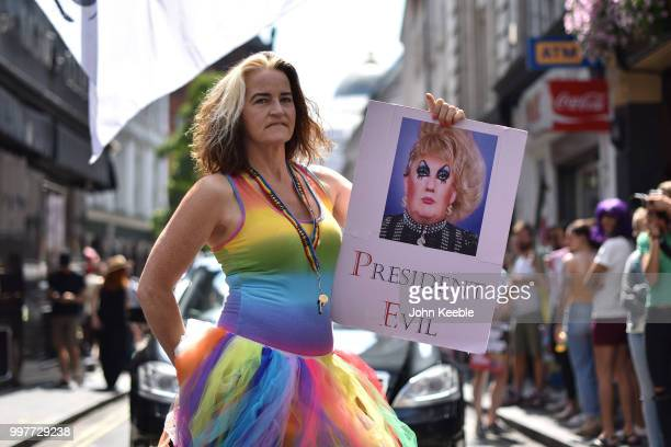 Demonstrator with an anti Trump placard saying President Evil attends the Drag Protest Parade LGBTQi March against Trump on July 13 2018 in London...
