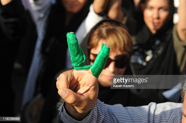 A demonstrator with green ribbon around his fingers flashes a Vsign during a peaceful march in Karimkhan Street Tehran 17th June 2009 The ribbon...
