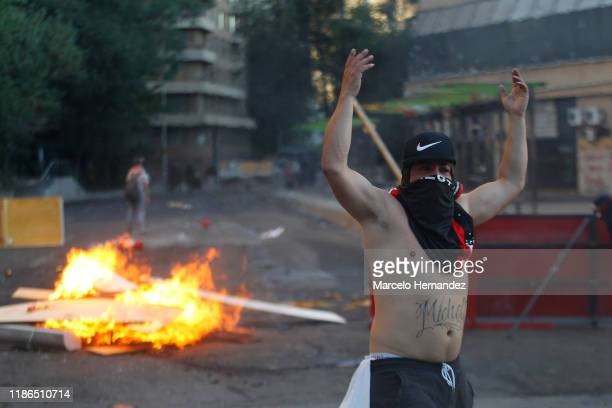 Demonstrator with his face covered reacts in front of a burning barricade during protests against president Piñera at Plaza Italia ona on December 4,...
