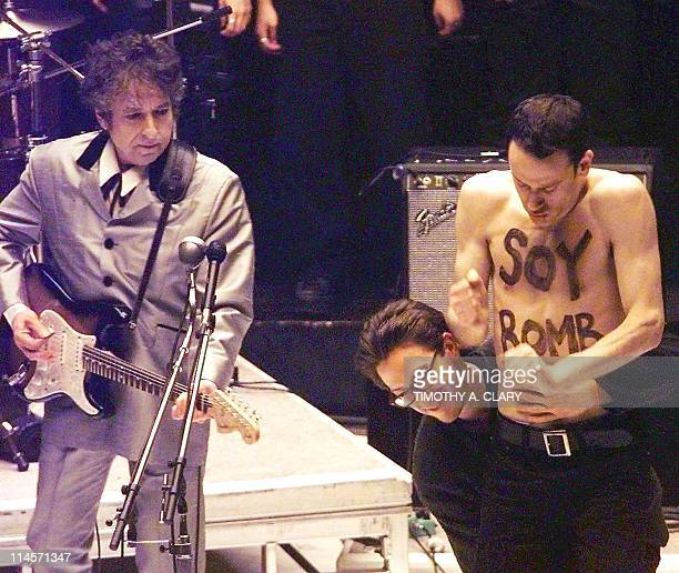 A demonstrator with 'Soy Bomb' painted on his chest is removed from the stage as Bob Dylan performs a song from his Grammy nominated album during the...