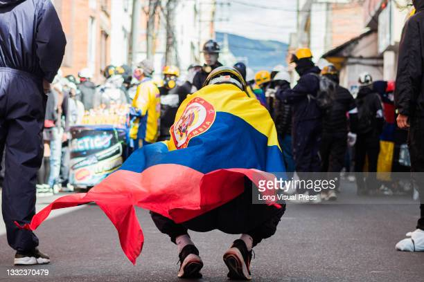 Demonstrator with the Colombian flag as demonstrations ended in late-night clashes between riot police and Demonstrators as Colombia marks 3 months...