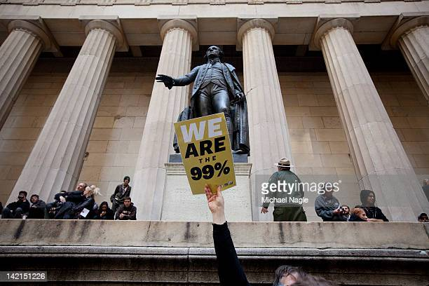 Demonstrator with the Occupy Wall Street holds up a 99% sign in front of the George Washington statue at Federal Hall during a rally on Wall Street...