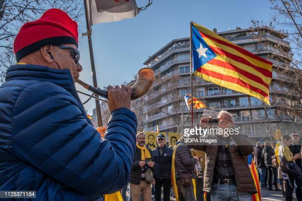 A demonstrator with the traditional Catalan cap barretina is seen blowing a horn next to a flag for the independence of Catalunya during the protest...