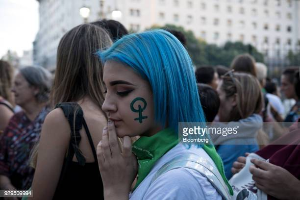 A demonstrator with the Venus symbol painted on her face attends a national strike On International Women's Day in Buenos Aires Argentina on Thursday...
