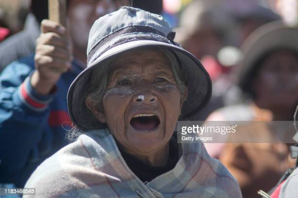 A demonstrator with white powder in his face shouts slogans against Interim President Jeanine Añez as supporters of Evo Morales Ayma clash with...
