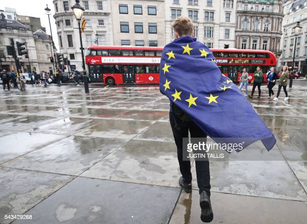A demonstrator wrapped in a European flag leaves an antiBrexit protest in Trafalgar Square in central London on June 28 2016 EU leaders attempted to...