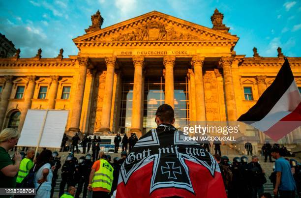 Demonstrator wrapped in a flag of the German empire faces off with riot policemen standing guard in front of the Reichstag building, which houses the...