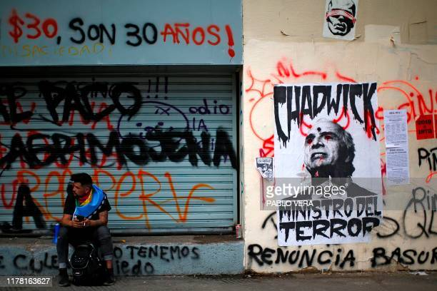 Demonstrator wrapped in a Mapuche indigenous flag sits near a poster depicting Chilean Minister of Interior and Public Security Andres Chadwick...