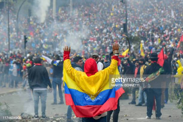 TOPSHOT A demonstrator wrapped in an Ecuadorean flag gestures during clashes with riot police outside the national assembly in Quito on October 8...
