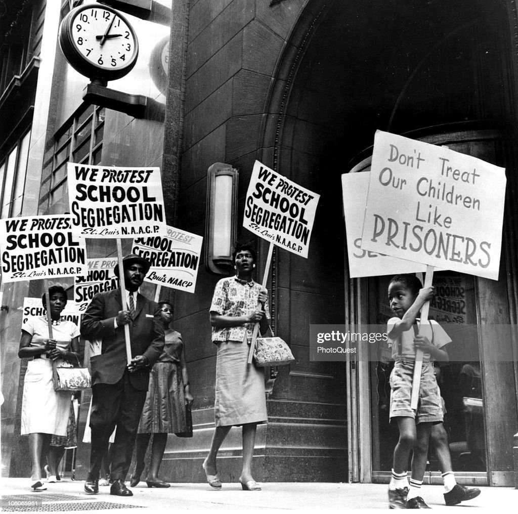Demonstrators, a young boy among them, picket in front of a school board office in protest of segregation, St Louis, Missouri, early 1960s.