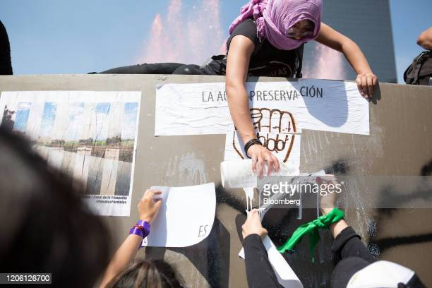 Demonstrators affix signs on a wall during a rally on International Women's Day in Mexico City Mexico on Friday March 8 2020 The United Nations first...