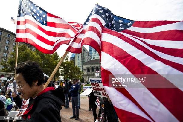 Demonstrators against Harvard University's admission process hold American flags while gathering during a protest at Copley Square in Boston...