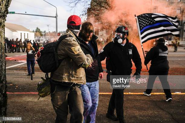 Demonstrators aid a Trump supporter who was beaten by counter-protesters during political clashes on December 12, 2020 in Olympia, Washington....