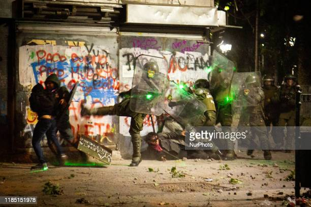 Demonstrators aim a laser beam against policem during a protest against the government in Santiago on November 27, 2019. The protest is against the...