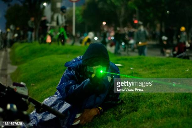 Demonstrators aim lasers to Colombia's riot police officers during anti-government that ended in clashes between protesters and Colombia's riot...