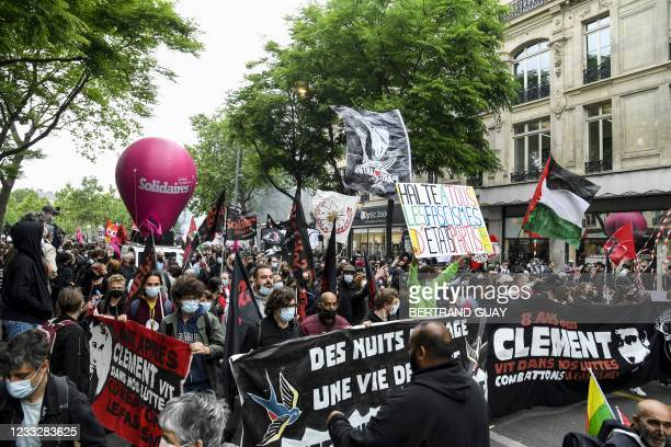 Demonstrators and anti-fascist activists hold banners depicting Clement Meric and wave flags during a demonstration in Paris, on June 5 a day after...