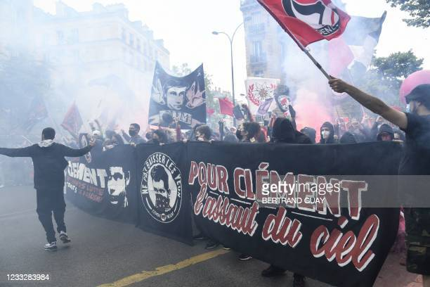 """Demonstrators and anti-fascist activists hold banners depicting Clement Meric and reading """"For Clement, an assault of the sky"""" amid smoke during a..."""