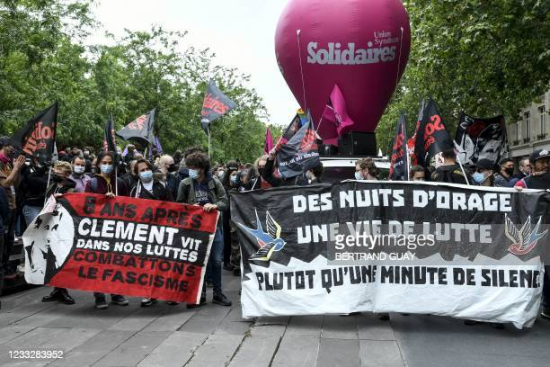 """Demonstrators and anti-fascist activists hold banners reading """"8 years later, Clement lives in our fights"""" and """"Storm nights and a life of struggle,..."""