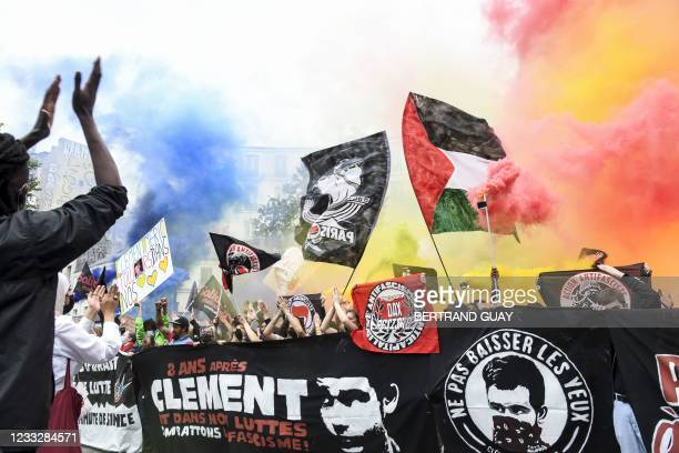 Demonstrators and anti-fascist activists light flares and hold banners depictin Clement Meric during a demonstration in Paris, on June 5 a day after...