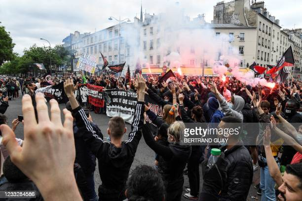 Demonstrators and anti-fascist activists light flares and hold banners during a demonstration in Paris on June 5 a day after two ex-skinheads...