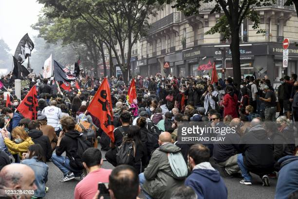 Demonstrators and anti-fascist activists sit on the ground in the street during a demonstration in Paris, on June 5 a day after two ex-skinheads...