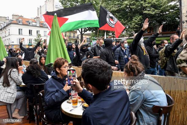 Demonstrators and anti-fascist activists walks past customers sitting at a restaurant's terrace during a demonstration in Paris, on June 5 a day...