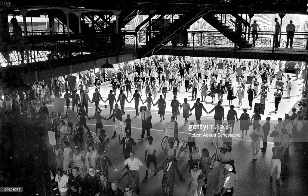 Demonstrators and Chicago Freedom Movement members march in lines, some with posters, under the Chicago El (elevated railroad) during a protest calling for the firing of School Superindentant Benjamin Willis by Mayor Daley over the former's delays in intergrating area schools, Chicago, Illinois, mid 1960s.