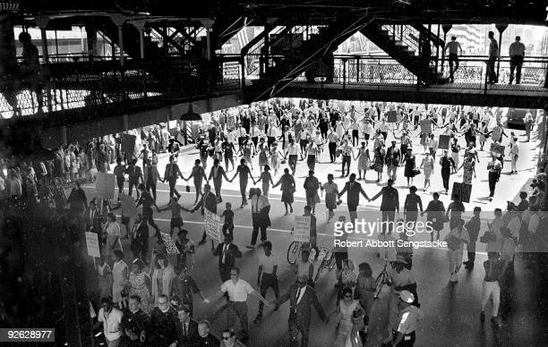 Demonstrators and Chicago Freedom Movement members march in lines, some with posters, under the Chicago El during a protest calling for the firing of...