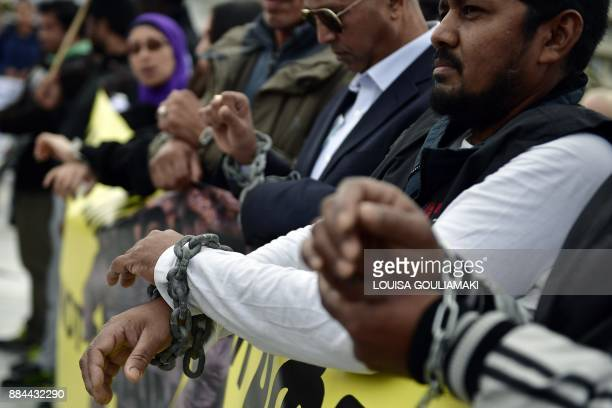 Demonstrators and migrants with their hands chained take part in a march towards the offices of the European Union on December 2 2017 in central...