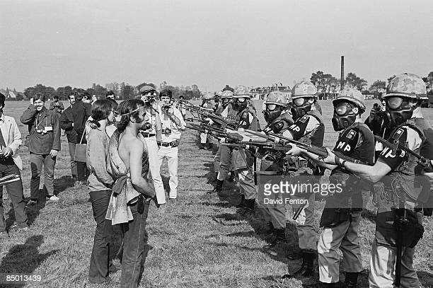 Demonstrators and photographers stand in front of a line of armed MPs from the United States First Army wearing gas masks and holding rifles with...