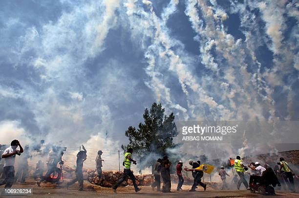 Demonstrators and photojournalists run for cover as Israeli soldiers fire teargas during a protest against the Israeli controversial separation...