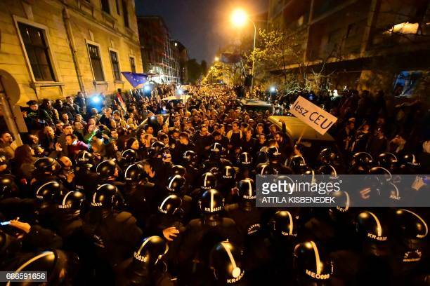 TOPSHOT Demonstrators are blocked by riot police officers near the headquarter of the governor FIDESZ party as students teachers of the Central...