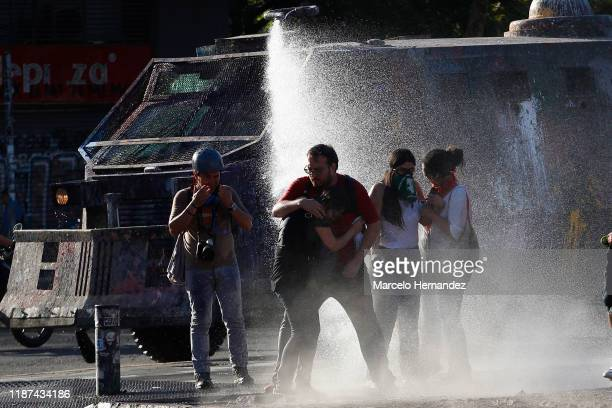 Demonstrators are contained by a water cannon during the protest against government of President Sebastian Piñera on December 09, 2019 in Santiago,...