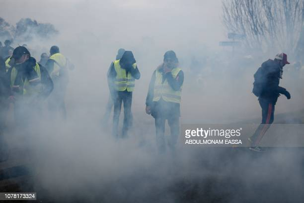 Demonstrators are engulfed by a cloud of teargas in Paris on January 5 during an antigovernment demonstration called by the yellow vest 'Gilets...